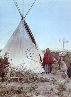 A Native American (Plains) woman, wearing a shawl, a print dress, and moccasins, poses next to a tepee with a child who wears a print dress - Smith-Hassell Co - Native American Horses, Native American Decor, Native American Pictures, Native American Beauty, Native American History, Indian Pictures, Native Indian, Native Art, Indian Tribes