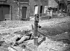 An American soldier lies dead beside water pump, killed by a German booby trap set in the pump in a French village on the Cherbourg Peninsula, on June 18, 1944. AP Photo