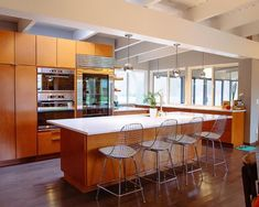 When remodeling a midcentury modern kitchen, consider updating the finishes, appliances, and storage while keeping the efficient layout.