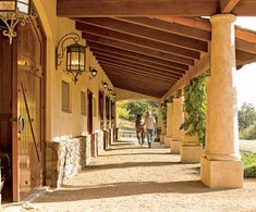 Leavengood walks a horse through the loggia of the 12-stall barn. The lanterns were fashioned by a blacksmith especially for the property.