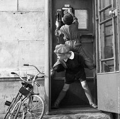 Two boys work together at a payphone 1961