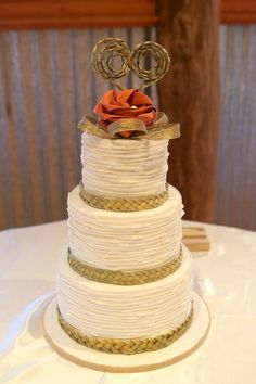 Flaxation woven heart cake topper with a single flower & gold loops. Woven natural flax cake bands.