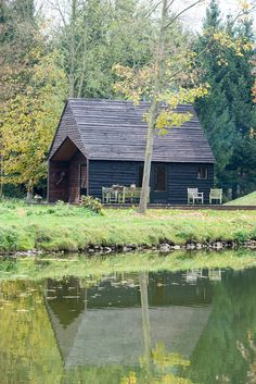 """This small black hut in Belgium is described by architecture studio De Rosee Sa as a """"magical lakeside cabin""""."""