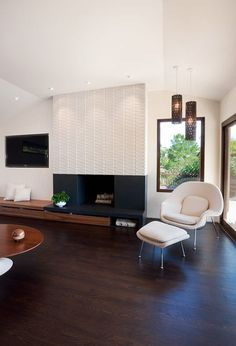 white.fireplace. cream seating. funktubular hanging lights. bench seating on wall by fireplace.