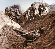 Up and at 'em! British soldiers  go into action, but the man in the foreground  has fallen before even leaving  the trench. Note the reinforced concrete bunkers in the background which have already suffered heavy artillery pounding