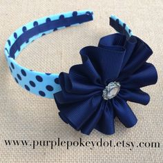 This darling headband is covered in light blue and navy polka dot fabric. Attached to headband is our shops signature jumble accessory in navy
