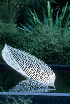Harpur Garden Images Ltd :: 06jhc12 100% Pure New Zealand garden. Silver-Gilt flora. Metal leaf sculpture by Virginia King floating on water. Xanthe White RHS Chelsea Show 2006. Contemporary Ornaments Ponds Jerry Harpur Please read our licence terms. All digital images must be destroyed unless otherwise agreed in writing. Photograph by: www.harpurgardenlibrary.com Contact: Harpur Garden Library 44 Roxwell Road Chelmsford Essex CM1 2NB, UK