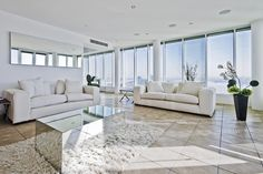 Large apartment modern living room with white furniture and floor-to-ceiling windows