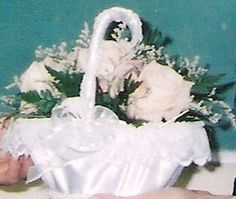 Flower girl basket is covered in white satin and trimmed with lace. The handle is wrapped with white satin ribbon. There are bows at each side of the handle where they join the basket.