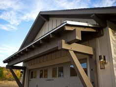 A timber trussing system, fashioned from Douglas fir, lends a rustic element and supports a corrugated metal overhang.
