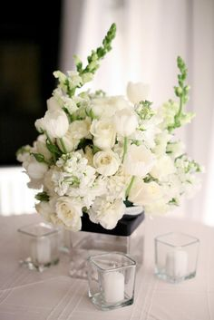 All-white centerpieces of tulips, roses, carnations and stock were surrounded by square votives for a modern, yet romantic look