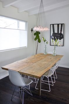 "We are obsessed with the dining room table. Tell us a bit more about it. Jasmine: ""I always wanted a large dining table, but couldn't find anything I loved that was in my price range. So, I decided to make it myself. I found two slabs of pine in Sebastopol, and found a guy that could weld the steel legs. A couple of days with a belt sander, I had myself a table."" The large wood table is offset by the white Eames and Bertoia chairs. Um, we can't get over that light fixture. Photographed by…"