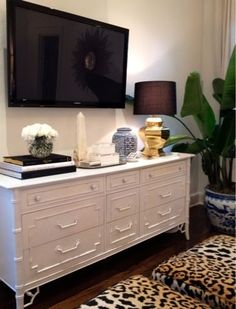 Bedroom. White Dresser Entertainment Center. Wall Mounted TV. No Wires. Blue and White. Chinoiserie. Gold Lamp. Fig Leaf Plant. Leopard Bed Stools.