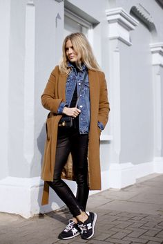 Camel jacket layered with a short denim jacket, leather trousers, crossbody bag and black trainers for a casual look | Image via  bloglovin.com