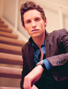 The man in this photo has the rare ability to make squatting by the stairs appear sensual. (Eddie Redmayne)