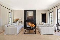 A blackened-steel fireplace anchors a serene Hamptons living room