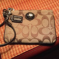Coach brown trim logo wristlet This is a coach brown logo wristlet. Fabric logo material brown leather trim and key fob. The wristlet is a lot more rate because it has the trade picture charm in front instead of just the stamp or name. Used maybe twice. No damage no wear no stains. 6 X 4 silver hardware and brown statin fabric inside. NO TRADES. NO LOWBALLS! Coach Bags Clutches & Wristlets