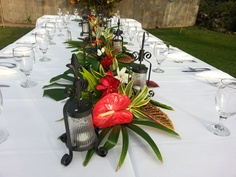 Tropical centerpieces with lanterns for a intimate wedding reception will add drama to a small table.