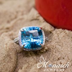 Nestled in the sand is an 18K white gold cushion cut 8.01 blue topaz ring. This ring has 230 diamonds (1.63cttw) and is VS2/SI1-FH quality. Item number RG912013. | Winter Park fine jeweler Monarch Jewelry 407-677-8354
