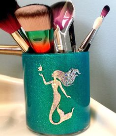 Custom made mermaid glass brush holder will add sparkle to your vanity Inside of brush holder is sealed to ensure no glitter will rub off or fall out onto your brushes or other items stored inside. Mermaid decal is available in holographic silver or metallic gold. I can customize the brush holder in several different colors. *Cover photo taken with flash please send me a message if you would like to order one with a metallic gold mermaid. Default is holographic silver