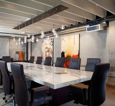 Crazy about this marble conference table with high-backed executive chairs; even the exposed cement is interesting, but probably too cold.: