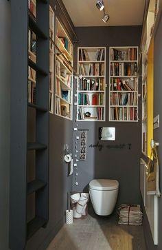 Alliance du pratique et de l'élégance, ces WC gris sont ornés de niches étagères blanches pour créer une bibliothèque aux toilettes.