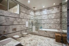 Luxurious pad: The master bathroom is entirely covered with granite tiles and features a j...