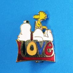 All you need is Love! Show your love on any outfit with a Snoopy pin. Find them in our shop at CollectPeanuts.com.