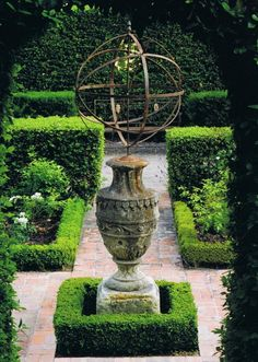 A traditional box-edged rose garden, paved by aged brick, framed by hedges of Viburnum tinus, surrounds a stone and iron armillary sphere…