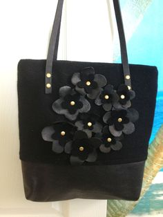 Recycled felt handbag with leather flowers and handles attached by brass rivets.