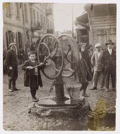 Otwock Poland. Two boys working the wheel of the town pump. 'The future of Otvotsk learns to pour water.' Doorways along the unpaved s... 1927