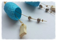 Long and dangle, these earrings are made from two turquoise coloured silk cocoons. They are very light and have two gold pearls and a ceramic ivory coloured fish bead hanging from a golden wire. Colorful Fish, Turquoise Color, Gold Pearl, Dangles, Mint, Ceramics, Drop Earrings, Beads, Button