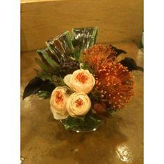 Orange Pin Cushion Protea, Black Calla, Artichoke, Peach Peony Roses in a Short Cylinder