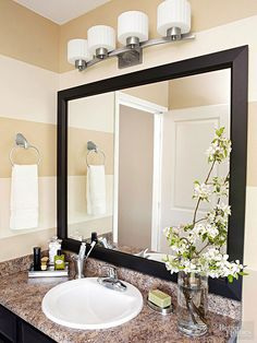 A custom black vinyl-over-MDF frame kit gives the plain-Jane frameless mirror a high-end look in minutes. A hefty new four-light fixture suits the scale of the large mirror and finishes the bath in style./