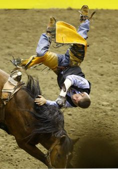 Chad Rutherford of McNeese State University flips over 'Shamrock' in the bareback event during the final performance of the 2014 CNFR on Saturday night in Casper. (Dan Cepeda, Star-Tribune)