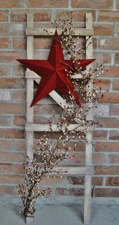 This Handmade 4 ft. tall Cedar ladder is decorated with Pip Berry Garland and an 18 Tin Star. Its painted with a Burgundy, Red and Beige Paint