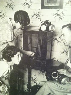 Late 1930's / early 1940's Listening to the Wireless. Note each person is holding a gas mask.
