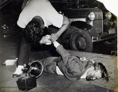 Many of Weegee's photographs, like this shot of a corpse being examined while…