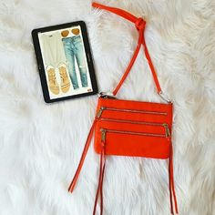 "Rebecca Minkoff Mini 3-Zip Rocker Crossbody Easily transitions from a clutch to a crossbody making it the style solution to your weekend adventures. • Color: Hot Orange  • Grained leather with polished silvertone hardware • Three exterior zip pockets with fringe pulls ; logo plaque at back • Top zip closure, • Clip removable shoulder strap with 23"" drop • Interior features signature logo printed cotton lining with patch pocket • Measures approximately 10'' width x 7 1/4'' tall x 1'' deep NWT…"