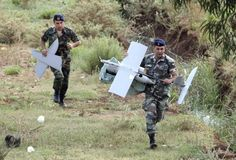 Lebanese Army soldiers carry parts of an Israeli drone in the Marjeyoun countryside, south Lebanon September 20, 2014. REUTERS-Karamallha Daher