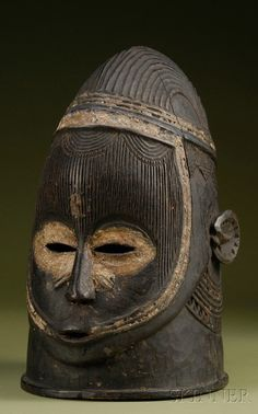 African Carved Wood Helmet Mask, Igala, pierced eyes and mouth, with elaborate scarification to face and neck, incised coiffure, with kaolin painted detail, dark patina, ht. 13 1/2 in.