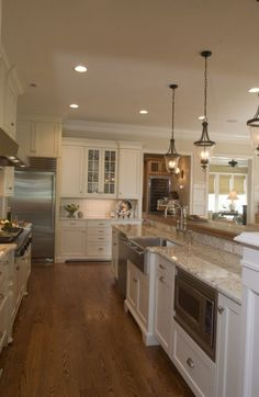 white cabinets, granite counter, pendants, island with apron sink