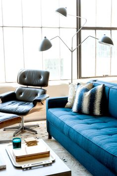 Eames lounge chair in modern, midcentury living room with Sputnik light fixture and blue sofa