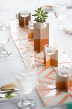 Runner of coasters and modern wooden voltive candle holders (via My Weddings).
