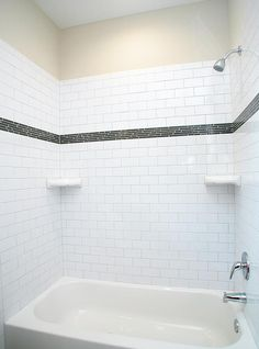 A Modern Style Tub With Subway Tile Surround With Glass Tile Accent Strip.  There Are