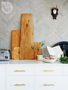 Grey concrete backsplash tiles laid in a herringbone pattern create a dramatic focal point in the kitchen. The irregularity of the tiles has a beautiful, rustic appearance.