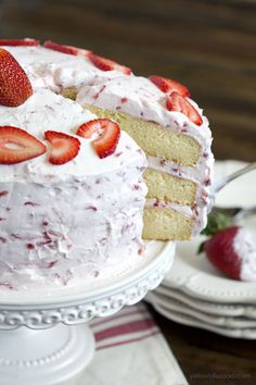 Fresh Strawberry Cake:  It's all about the frosting - fresh whipped cream and cream cheese + fresh strawberries in every bite! All surrounding a moist, tender vanilla cake. #cakebaking