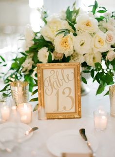 Wedding table ideas on a budget. Achieve the classic-clam look with a golden frame some votives and a delicate flower arrangement in white and green like at this stunning West Hollywood wedding. Photography: Jose Villa Photography.