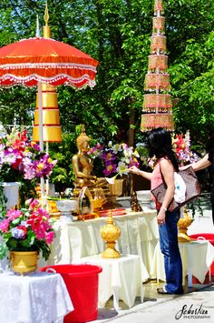 Fellow temple goers wash the Buddha statue with holy water for good luck & blessings at a Lao temple during Lao New Year.