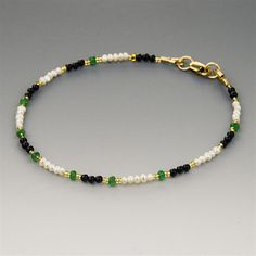 This delicate gemstone bracelet features tiny (2.5mm) genuine natural emeralds in the most hard-to-find and sought-after shade of grass green. The emeralds are translucent, and have been strung with another rarity, high quality tiny (2-2.5mm) real cultured white seed pearls, as